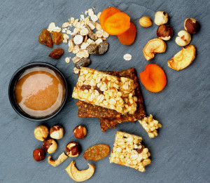 Arrangement of Useful Granola Bars with Muesli, Nuts, Dried Apricots and Bowl of Honey closeup on Black Stone background. Top View