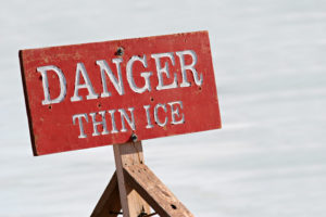 danger thin ice - warning sign by a lake
